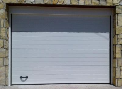 Puerta seccional acanalada blanca ral 9016 dos caras, de paneles de 40mm espesor, formados por chapa de acero galvanizado y prelacado ambas caras, rellenos en su interior de espuma aislante de poliuretano expandido de alta densidad (40Kg/m3), guias en ace