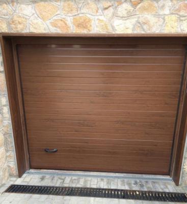 Puerta seccional acanalada madera clara/oscura dos caras, de paneles de 40mm espesor, formados por chapa de acero galvanizado y prelacado ambas caras, rellenos en su interior de espuma aislante de poliuretano expandido de alta densidad (40Kg/m3), guías en