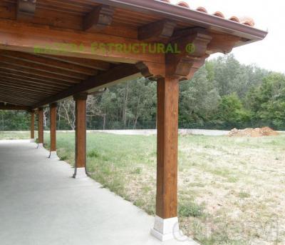 Porche adosado con estructura de madera lasurada, basas de granito para los pilares y cubrición de teja cerámica mixta. Precio desde 115 € por m².